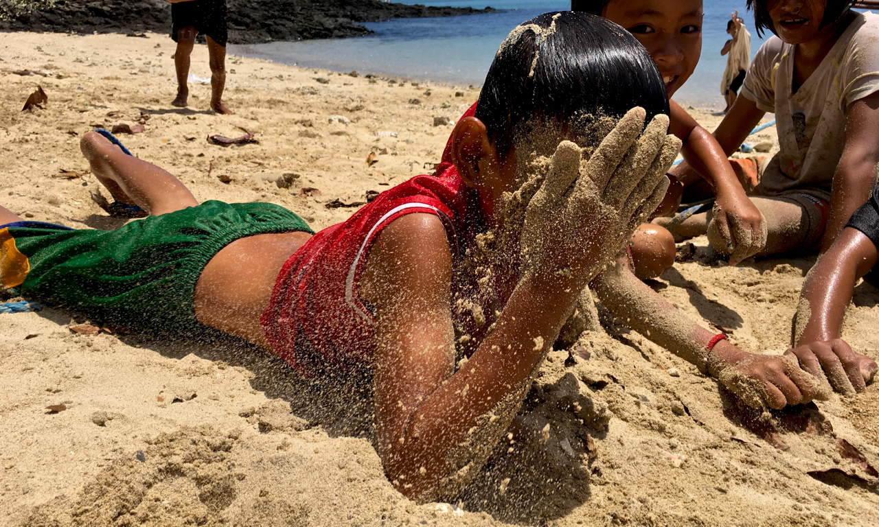 island kid covering his face with sand